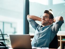Mann sitzt glücklich vorm Laptop