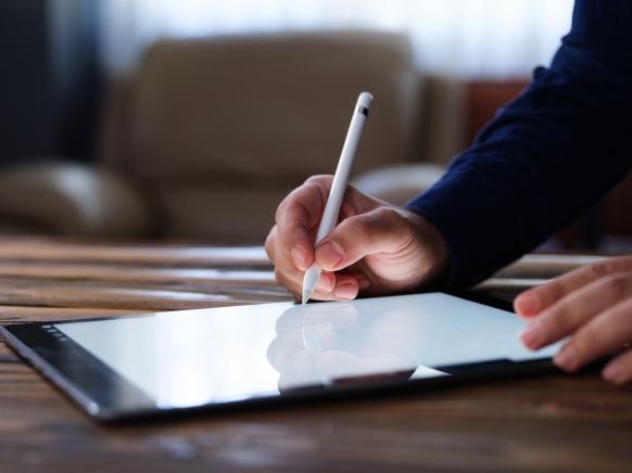 Person unterschreibt am Tablet