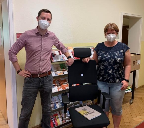 Zwei Personen stehen neben einem Bürodrehstuhl
