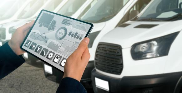 Person steht mit Tablet vor Autos