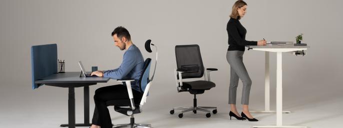 Personen arbeiten an höhenverstellbaren Tischen